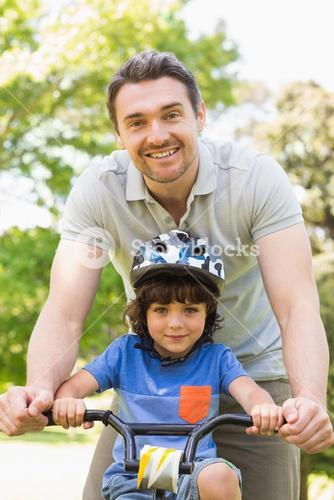 Man teaching his son to ride a bicycle