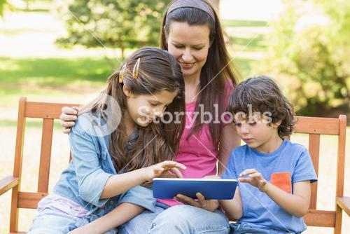 Woman with kids using digital tablet in park