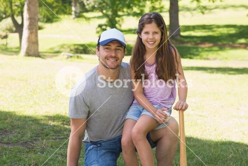 Father and daughter holding baseball bat in park