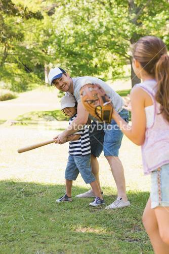 Family playing baseball in park