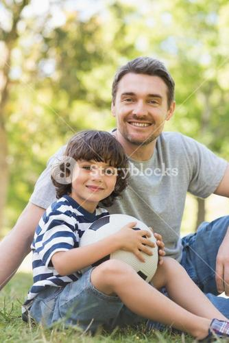 Father and son with football sitting on grass inpark