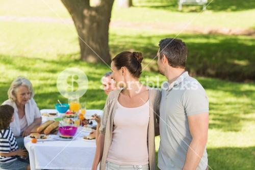 Couple with family dining at outdoor table