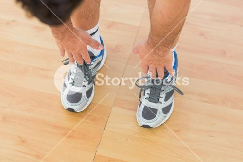 sporty man stretching hands to legs in fitness studio
