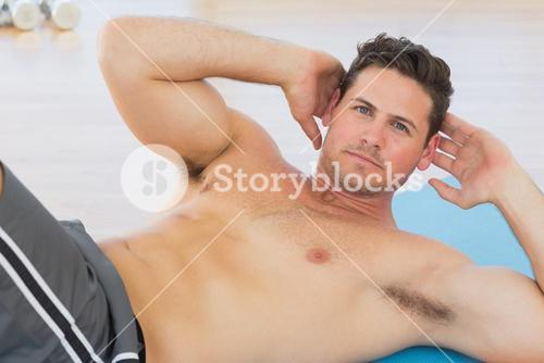 Determined young man doing abdominal crunches