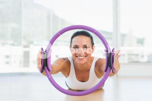 Sporty woman with exercise ring in fitness studio