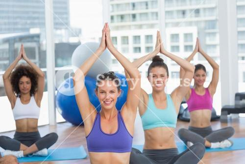 Sporty people in Namaste position at fitness studio