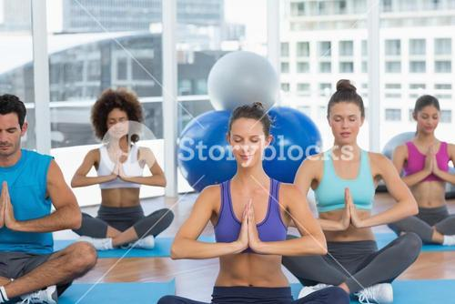Sporty young people in Namaste position with eyes closed
