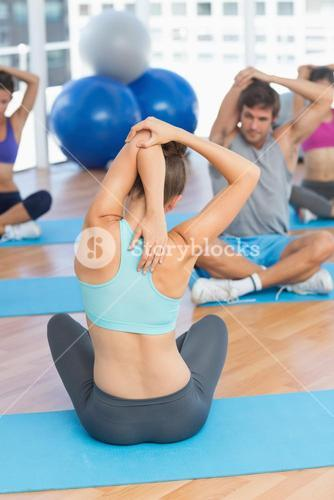 People with trainer stretching hands behind backs