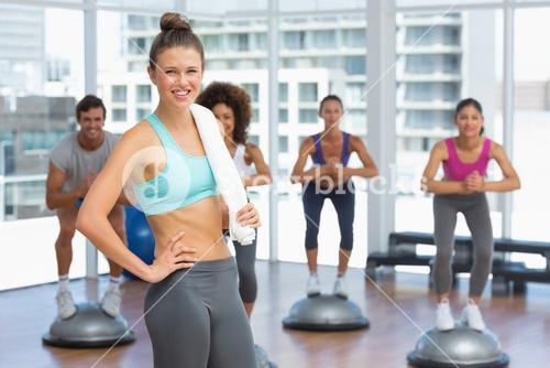 Smiling woman with fit people performing step aerobics exercise