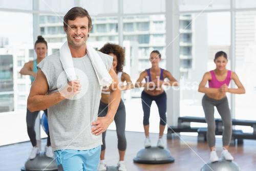 Man with fit people performing step aerobics exercise