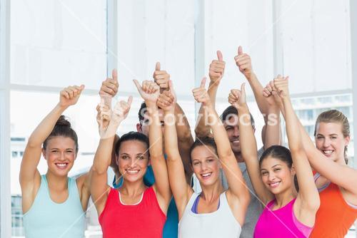 Fit people gesturing thumbs up in exercise room