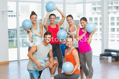 Fit young people with balls in exercise room