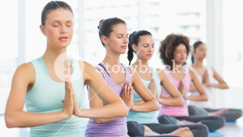 Young sporty women with joined hands sitting in row