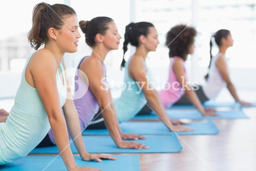 Side view of a fit class doing the cobra pose