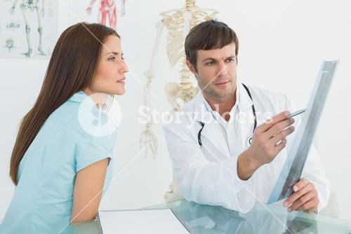 Doctor explaining xray to female patient in the medical office