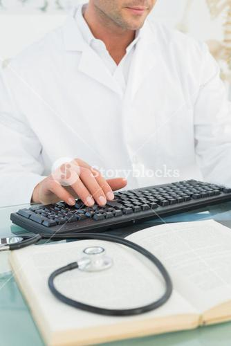 Mid section of a male doctor using computer
