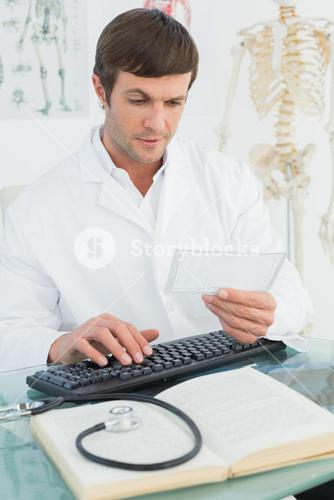 Doctor reading a note at desk in medical office