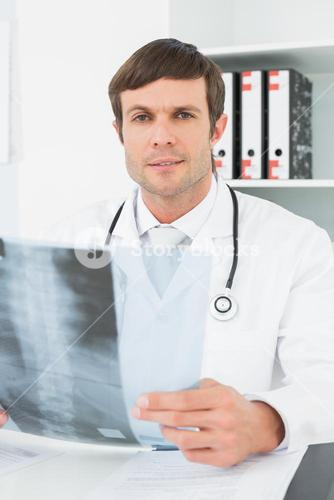Doctor with xray picture of spine in the medical office