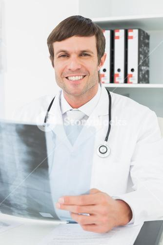 Smiling doctor with xray picture of spine in the medical office