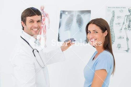 Smiling male doctor explaining lungs xray to female patient