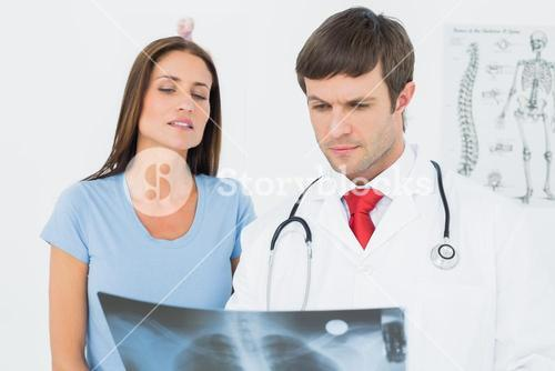Male doctor explaining lungs xray to female patient