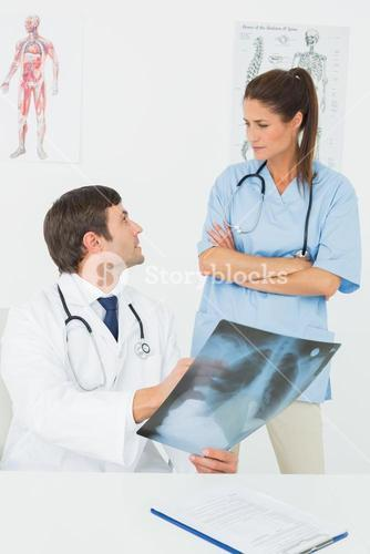 Male doctor and female surgeon examining xray