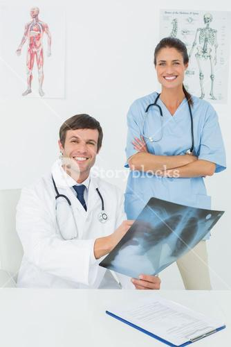 Portrait of doctors examining xray in medical office