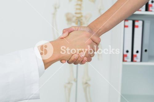 Extreme closeup of a doctor and patient shaking hands