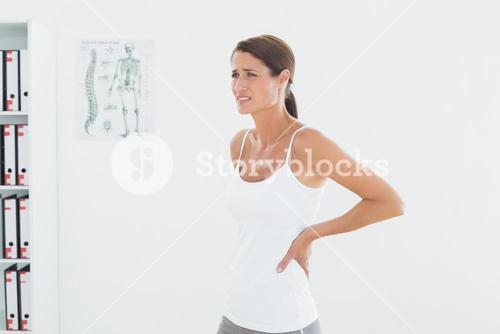 Side view of a beautiful young woman with back pain