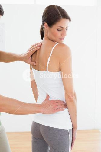 Physiotherapist examining womans back in medical office