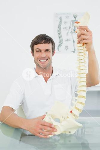 Smiling male doctor holding skeleton model