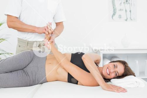 Doctor examining a patients hand in medical office