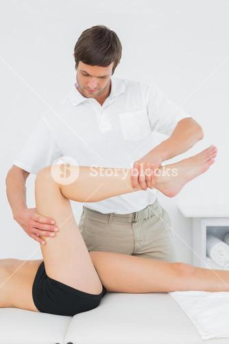 Male physiotherapist examining a young womans leg