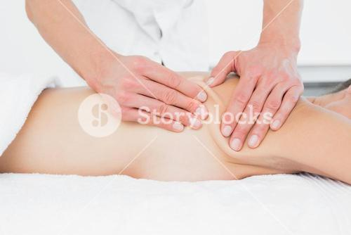 Mid section of a physiotherapist massaging womans body