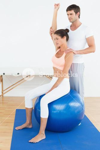 Woman on yoga ball while working with physical therapist