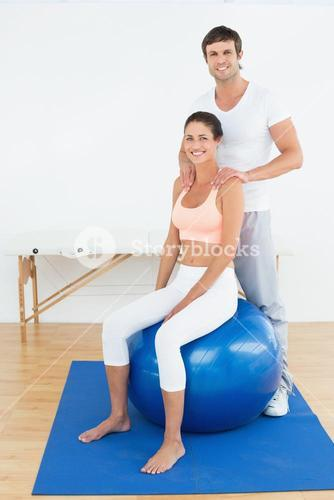 Woman on yoga ball working with physical therapist
