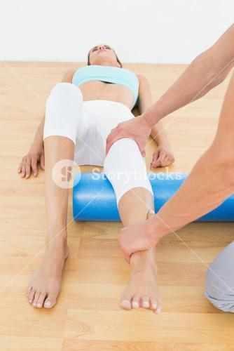 Physical therapist examining a young womans leg