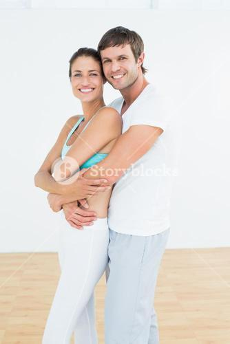 Fit couple embracing in fitness studio