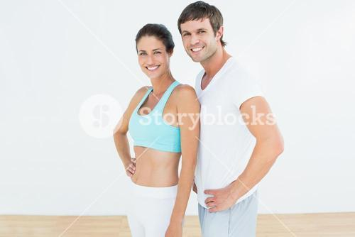 Portrait of a fit couple in fitness studio