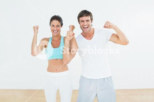Cheerful fit couple clenching fists in fitness studio