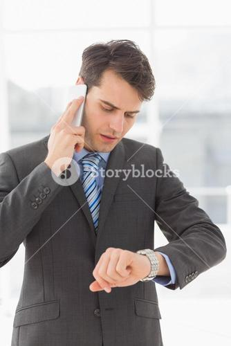 Serious businessman checking the time while on the phone