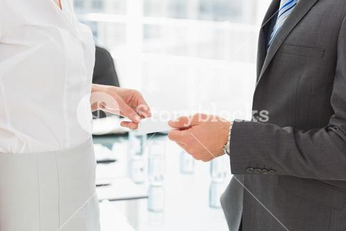 Businessman handing businesswoman a card