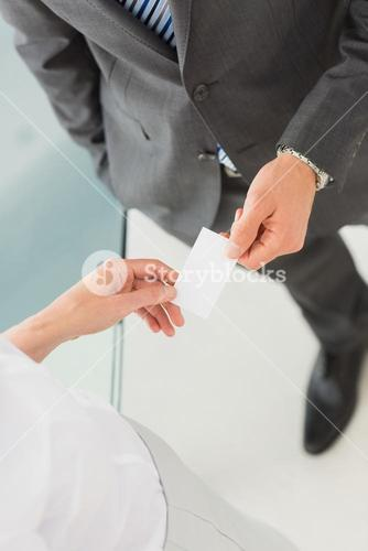 Businessman handing businesswoman his card