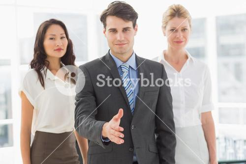 Happy businessman reaching hand out in front of his team
