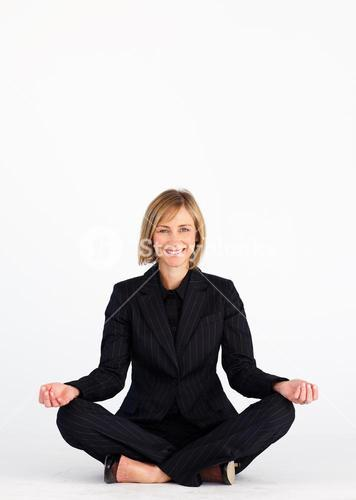 Smiling mature businesswoman doing yoga exercises