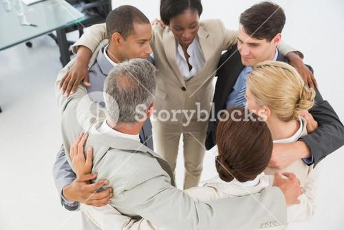 Diverse business team hugging in a circle