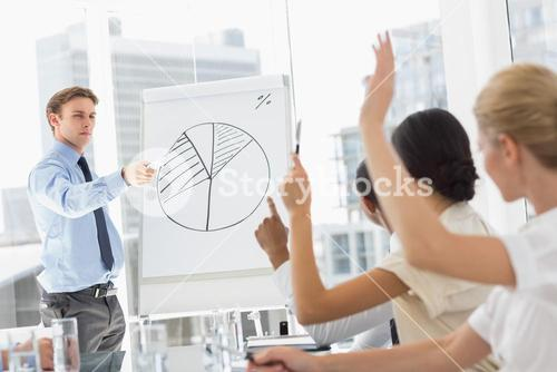 Businessman presenting pie chart to colleagues asking questions