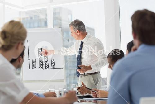 Senior businessman presenting bar chart to his colleagues