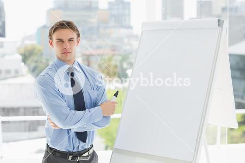 Young stern businessman standing by whiteboard