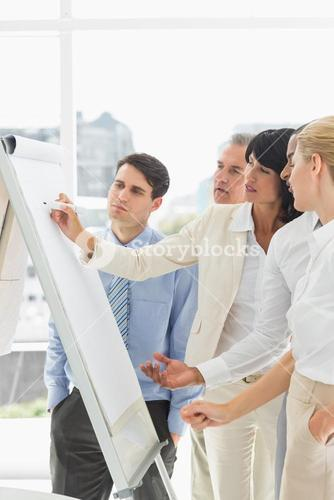 Interested colleagues watching businesswoman writing on whiteboard